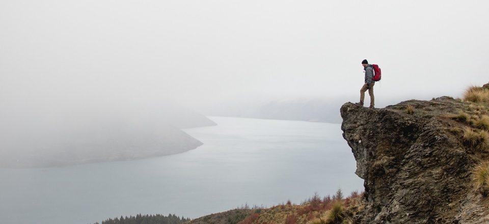 En person står på en klippa och spanar ut över ett dimmigt landskap