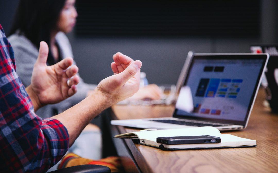 Två händer gestikulerar vid ett mötesbord med en dator