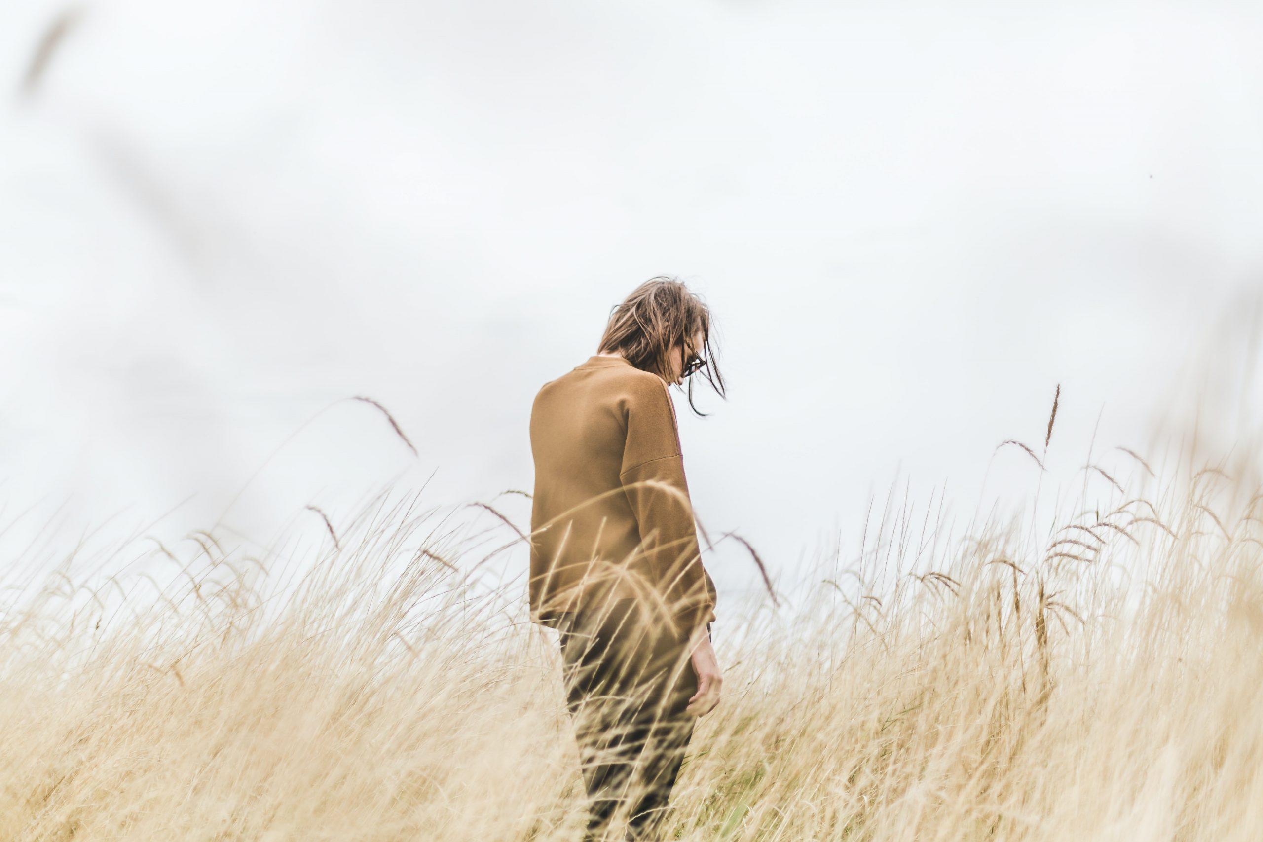 En person står med ryggen mot kameran i högt gult gräs