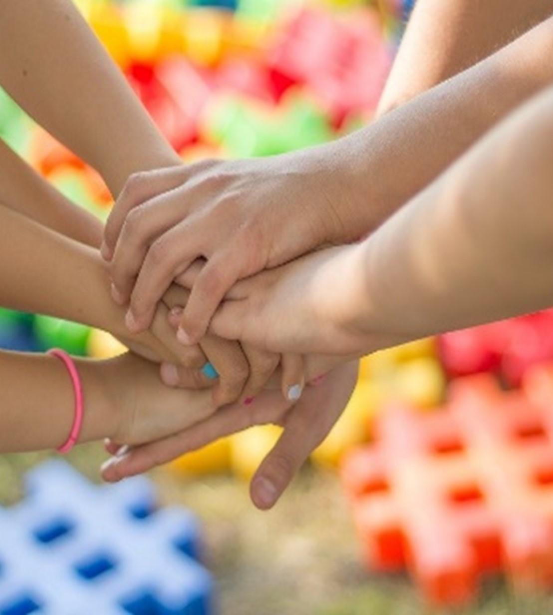 Barnhänder som sträcks fram och håller i varandra