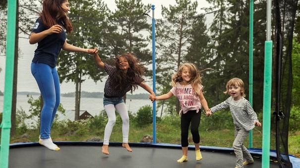 Fyra barn hoppar i en studsmatta