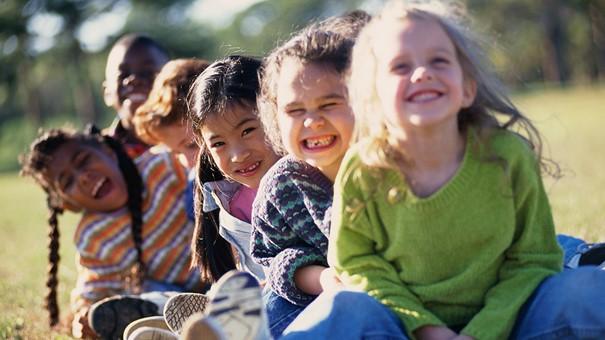 Glada barn som sitter i en lång rad